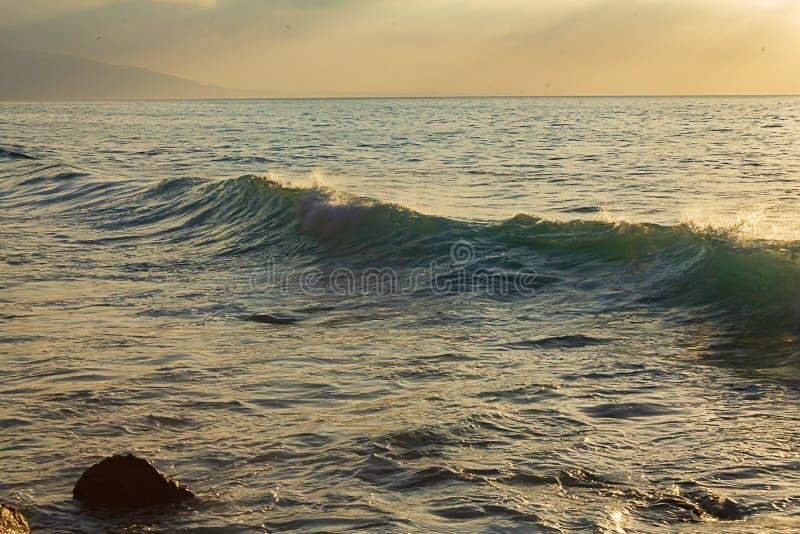 A parede de ondas escuras saindo do oceano se expande com espuma e lavagem das costas se formando contra o mar brilhante foto de stock