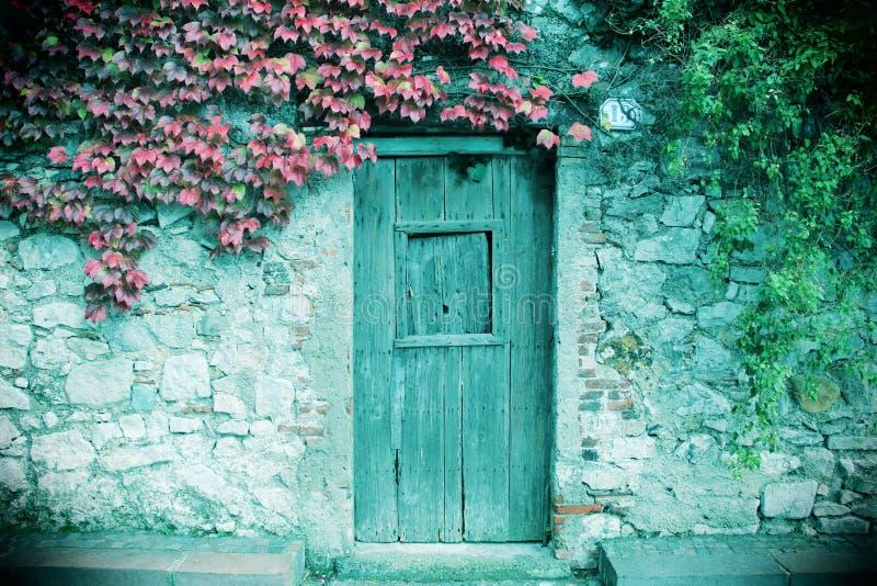 Parede de pedra antiga e uma porta fechado de madeira imagens de stock
