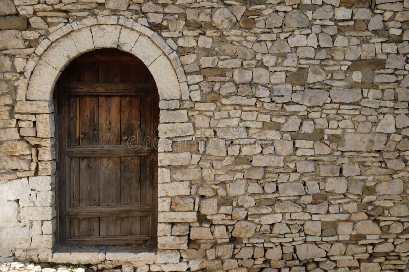 Parede de pedra com a porta de madeira velha na cidade velha Berat, Albânia fotografia de stock