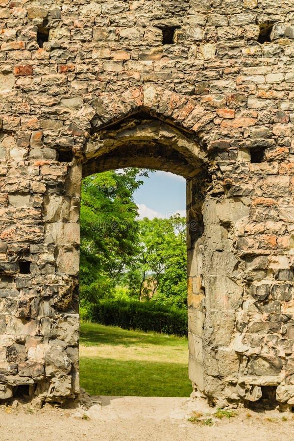 Parede de pedra com portal em um jardim imagens de stock