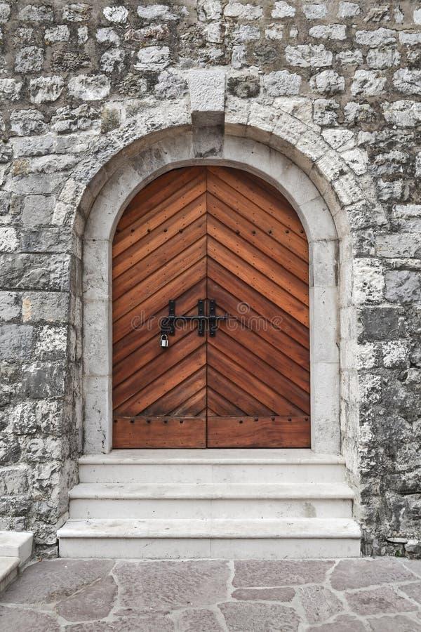 A parede de pedra da fortaleza do castelo do castelo medieval, uma porta fechado de madeira velha com um fechamento imagens de stock