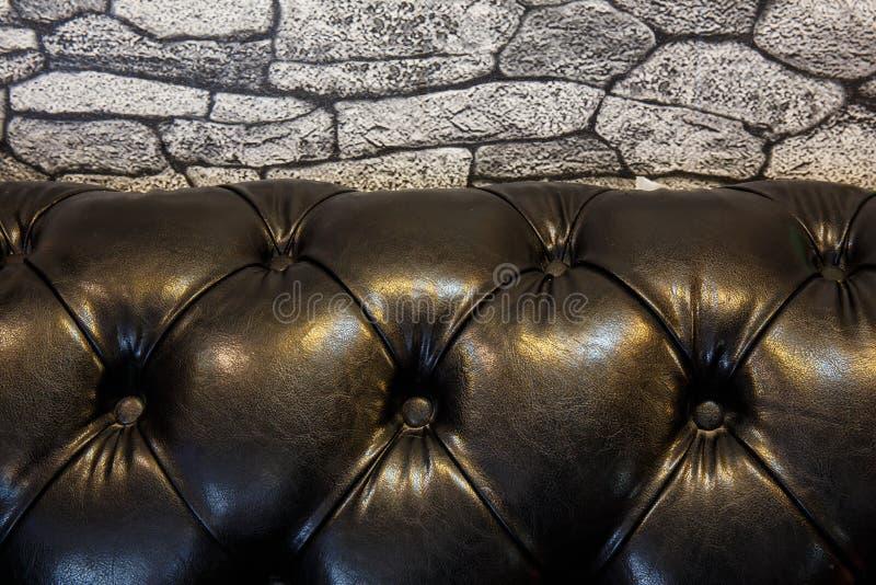 parede de pedra e sofá de couro preto foto de stock royalty free