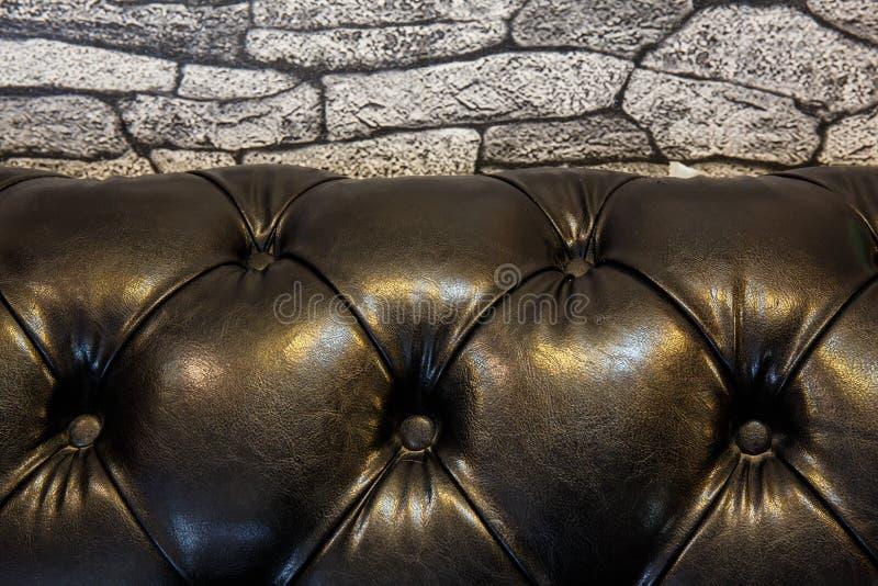 parede de pedra e sofá de couro preto fotos de stock royalty free