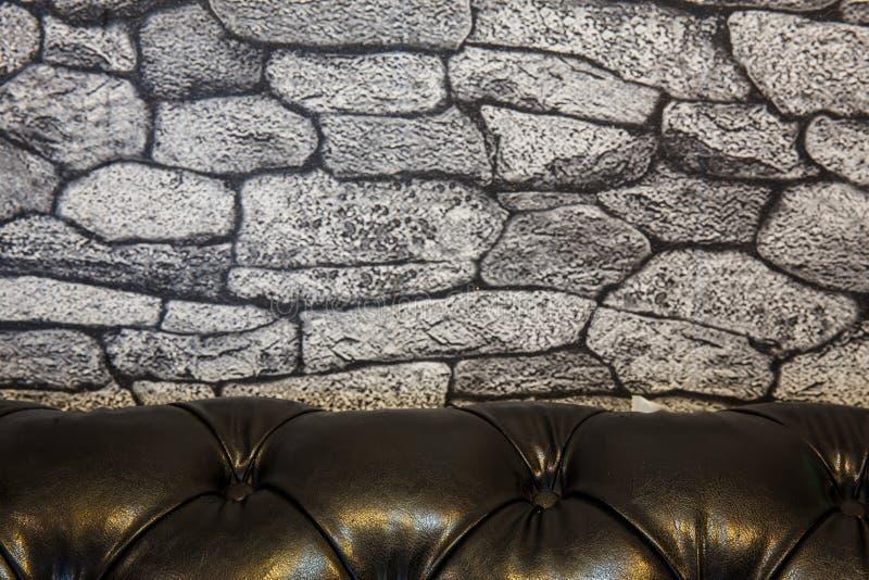 parede de pedra e sofá de couro preto imagens de stock royalty free