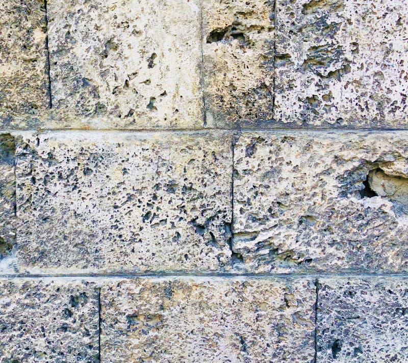 Parede de pedra envelhecida deteriorada velha da rocha de uma construção antiga fotos de stock royalty free