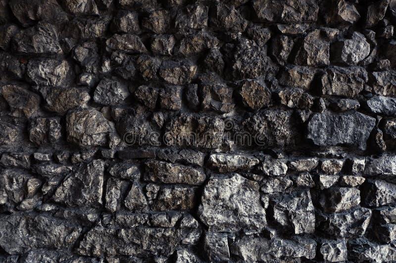 Parede de pedra escura feita de rochas irregulares e ásperas fotos de stock