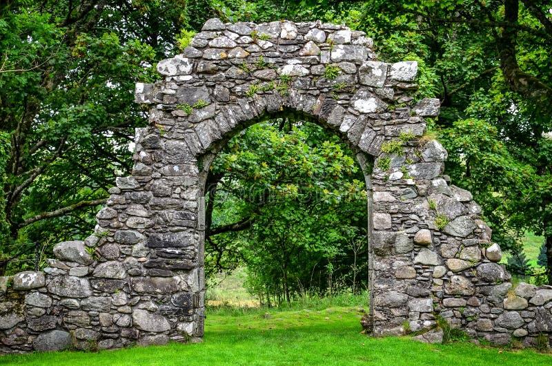 Parede de pedra velha da entrada no jardim verde fotos de stock