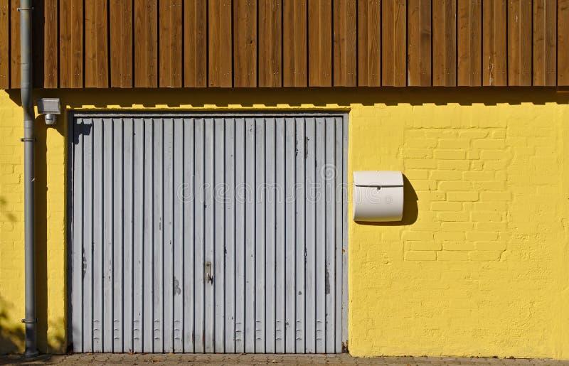 Parede de tijolo amarela com porta da garagem, caixa postal, downspout e paneling de madeira no segundo andar fotografia de stock