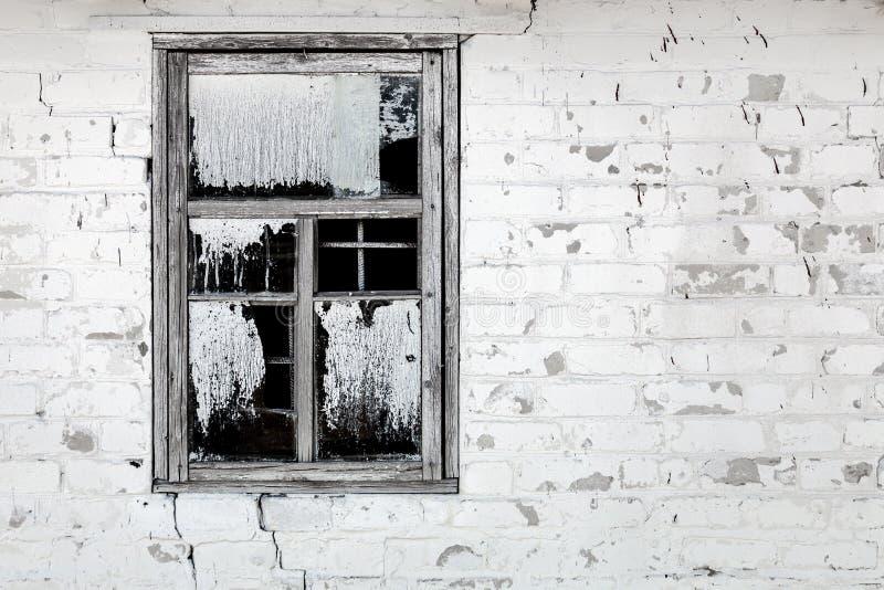 Parede de tijolo branca rachada envelhecida velha com janela quebrada Grelhas sujas quebradas do vidro e do ferro de janela com f imagens de stock royalty free
