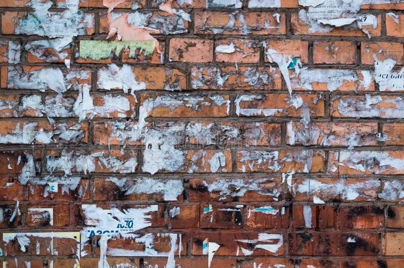 Parede de tijolo com anúncios rasgados Brown Brickwall colou aleatoriamente e raspou etiquetas imagem de stock royalty free