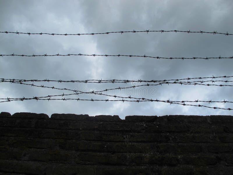 Parede de tijolo com arame farpado, contra um céu nebuloso escuro foto de stock