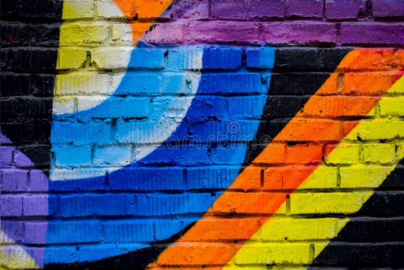 Parede de tijolo com fragmento dos grafittis, close-up abstrato da arte dos desenhos Para o fundo Cultura urbana icónica moderna fotos de stock royalty free
