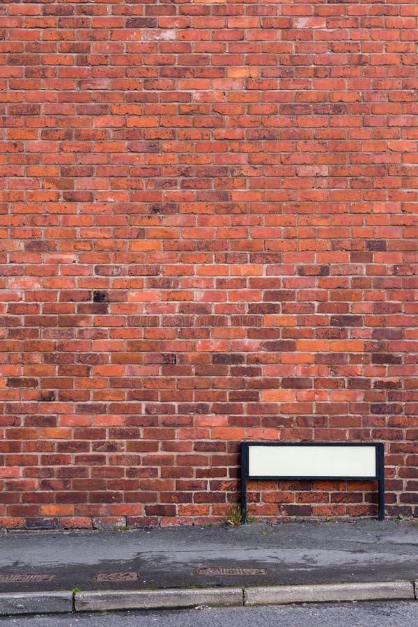 A parede de tijolo com pavimento e assina dentro a parte dianteira foto de stock royalty free