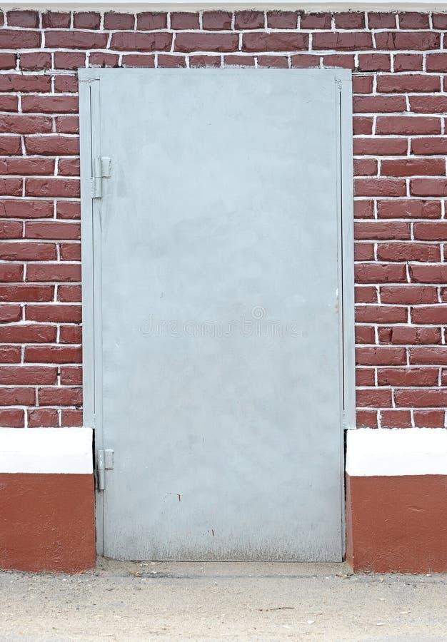 Parede de tijolo com porta do metal imagens de stock royalty free