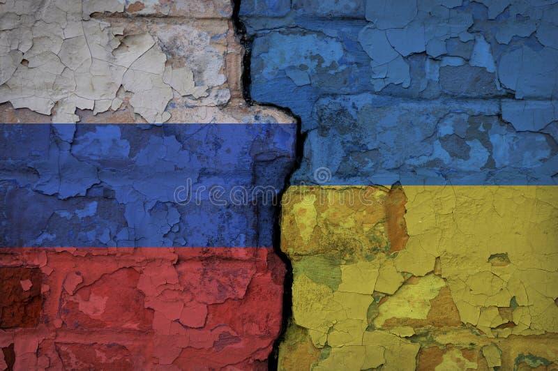 Parede de tijolo com uma quebra pintada em lados opostos nas bandeiras ucranianas e do russo imagens de stock