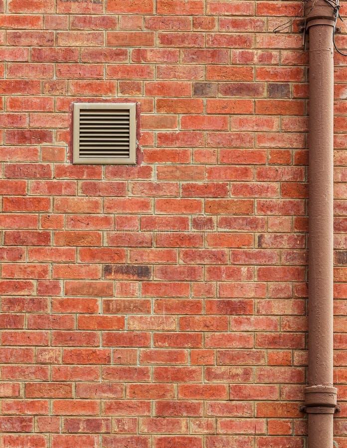 Parede de tijolo de Brown com respiradouro e a tubulação velha imagens de stock