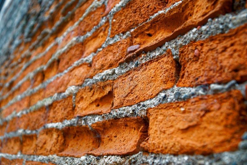Parede de tijolo gasta com blocos golpeados vermelhos feitos sob medida diferentes foto de stock