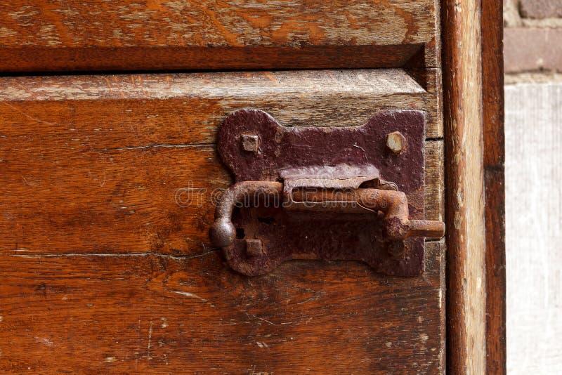A parede de tijolo marrom oxidada do fechamento de madeira velho da fechadura da porta do vintage forjou a captura de madeira do  fotos de stock