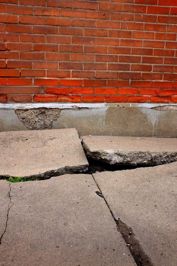Parede de tijolo rachada quebrada velha do passeio do cimento fotografia de stock