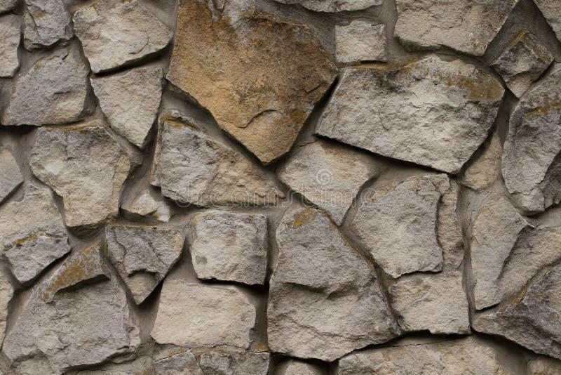 Parede de tijolo de um fim selvagem da pedra acima do fundo Textura antiga cinzenta da pedra imagens de stock