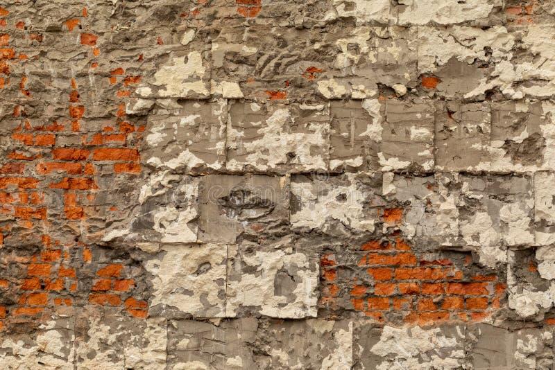 Parede de tijolo velha com emplastro e concreto destru?dos Desmontando a constru??o imagem de stock