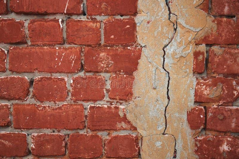 Parede de tijolo vermelho com emplastro rachado abstraia o fundo imagens de stock royalty free
