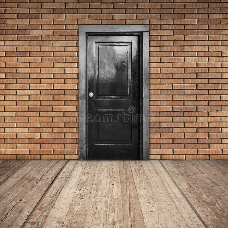 Parede de tijolo vermelho, porta preta e assoalho de madeira fotografia de stock royalty free