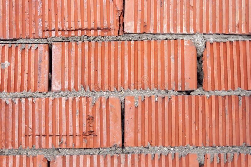 Parede de tijolos listrados alaranjados com uma camada grossa de cimento entre eles fotos de stock royalty free