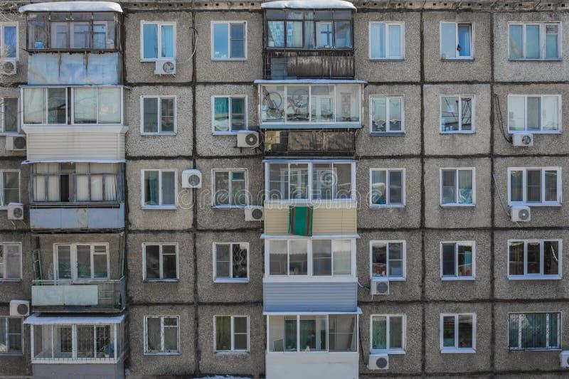 A parede de uma casa dilapidada com janelas e balcões imagem de stock royalty free