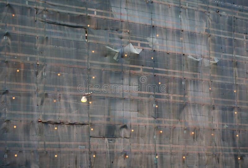 Parede de uma construção residencial com grade protetora iluminada do andaime e da fachada imagens de stock