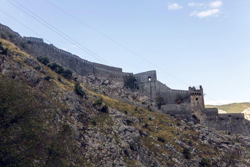 Parede de uma fortaleza de pedra velha pela água fotos de stock