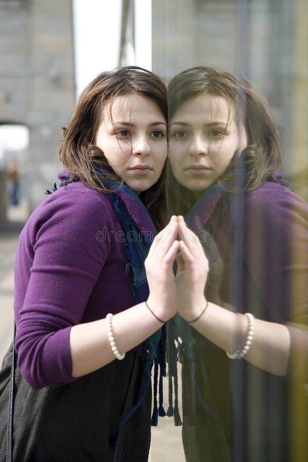Parede de vidro próxima ao ar livre da menina adolescente séria nova imagens de stock