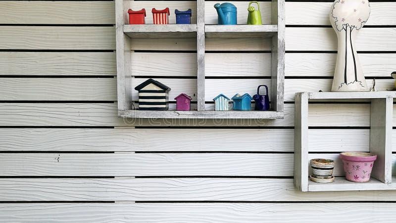 A parede decorativa com prateleira faz da madeira branca no fundo da textura do jardim imagem de stock royalty free
