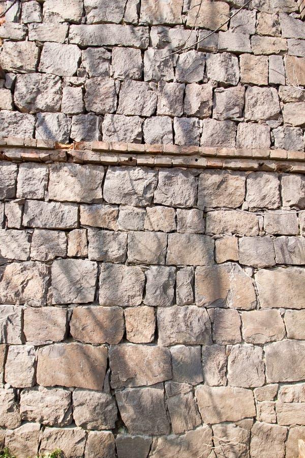 Parede do bloco do granito, de pedras diferentes da forma, em um dia ensolarado, foto arquitetónica da textura abstrata áspera da fotografia de stock