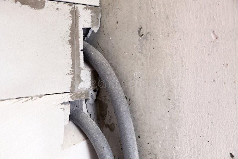 Parede do close up do concreto ventilado cinzento com as emendas ásperas com furo para as tubulações de água no isolamento Revisã imagens de stock royalty free