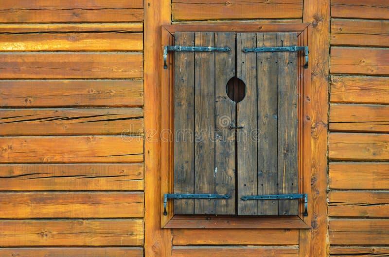 Parede do log com os obturadores de madeira fechados da janela fotografia de stock royalty free