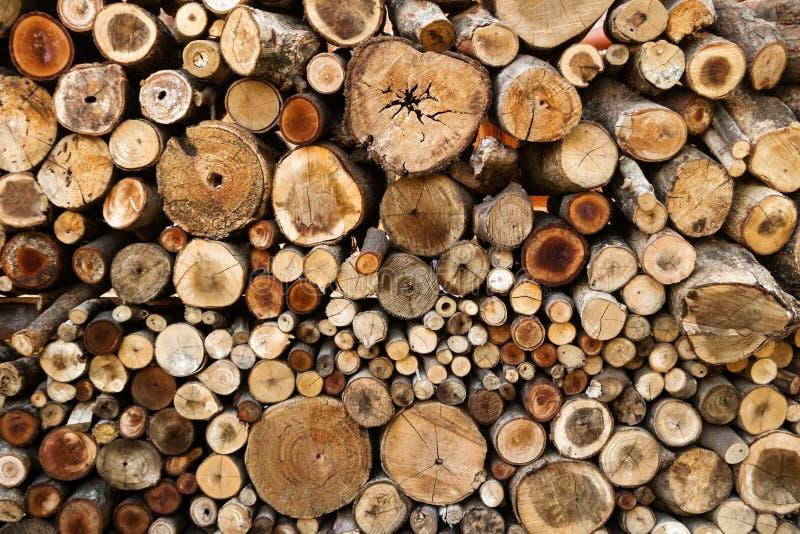 Parede dos logs desbastados secos da lenha empilhados acima sobre se em uma pilha Textura de madeira do Close-up fotografia de stock