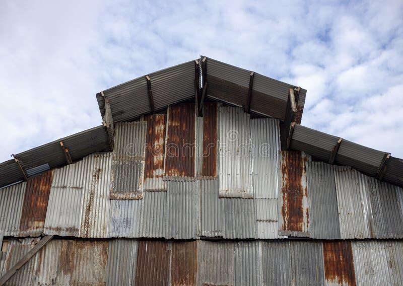 Parede e telhado rústicos da construção da placa do ferro no fundo do céu Armazém simples Parede e telhado feitos de ferro ondula fotos de stock royalty free