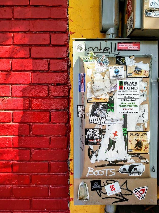 Parede Exterior Colorida de Construção de Tijolos Urbanos com Caixa Elétrica e Adesivos de Graffiti foto de stock