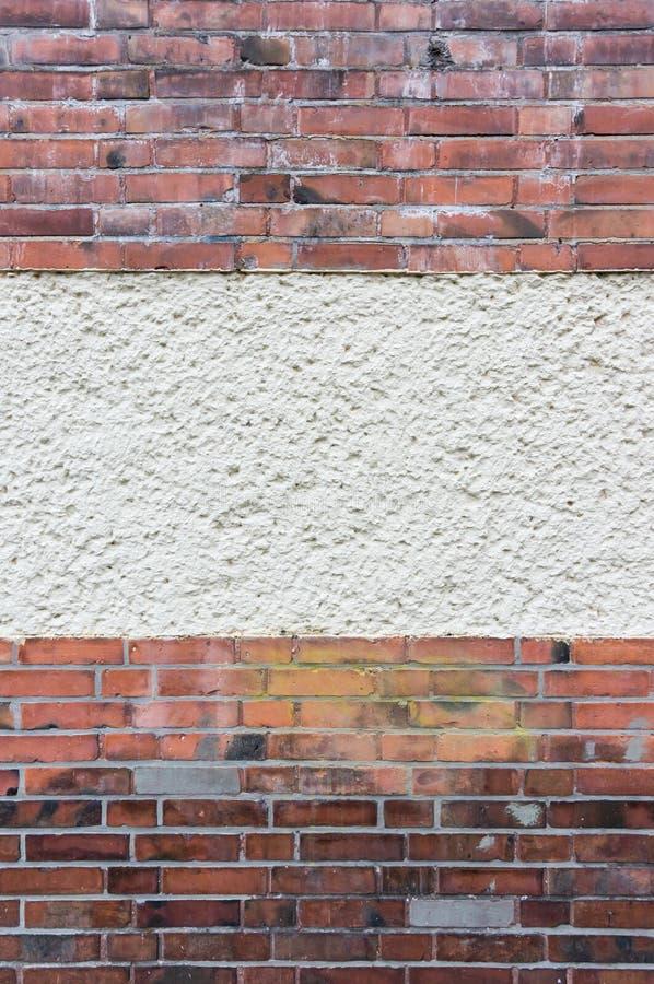 Parede exterior com área emplastrada entre o tijolo de clinquer vermelho imagens de stock