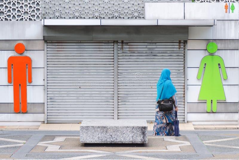 Parede exterior com sinais dos homens e das mulheres separados por uma porta Wc do ícone imagens de stock