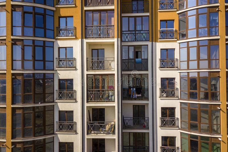 Parede exterior do detalhe do apartamento ou do prédio de escritórios Os trilhos forjados do balcão, céu azul refletiram em janel imagens de stock royalty free