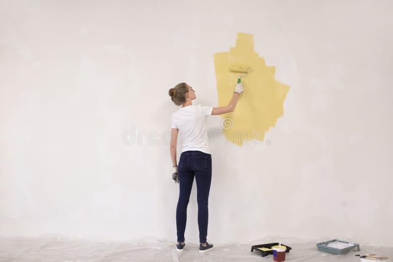 Parede fêmea da pintura do decorador com rolo dentro imagens de stock royalty free