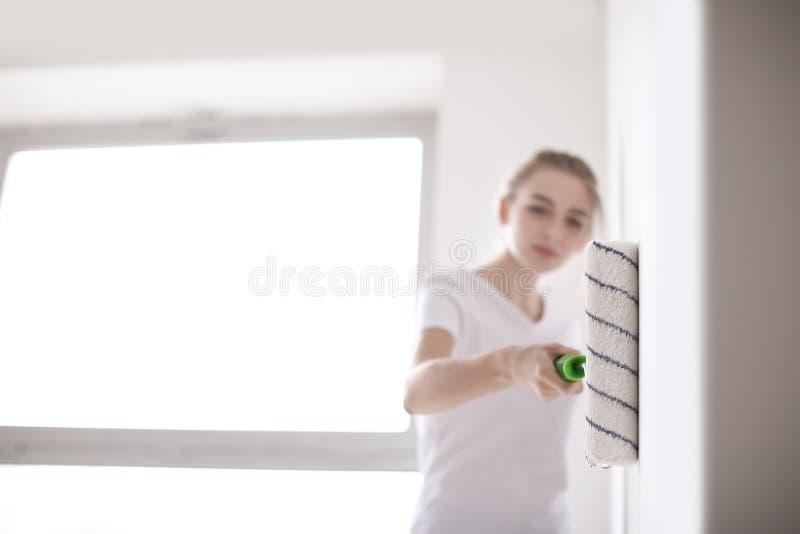 Parede fêmea da pintura do decorador com rolo dentro foto de stock