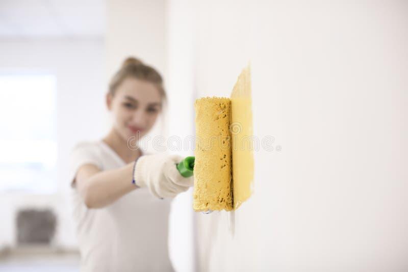 Parede fêmea da pintura do decorador com rolo dentro fotografia de stock royalty free