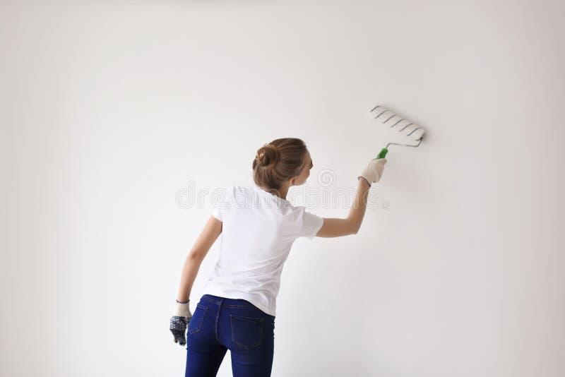 Parede fêmea da pintura do decorador com rolo dentro imagem de stock royalty free