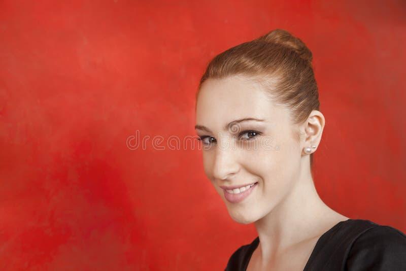 Parede fêmea de Smiling Against Red do dançarino de bailado imagens de stock