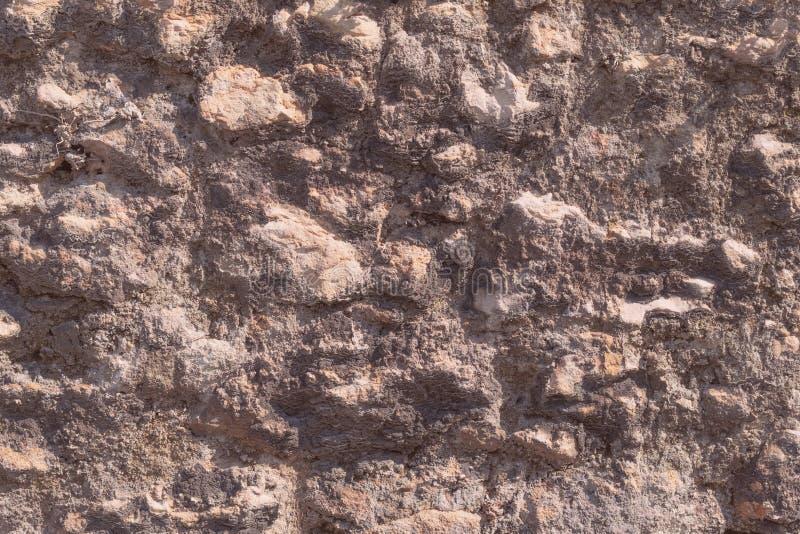 A parede ? feita da pedra e do cimento naturais desiguais imagem de stock royalty free