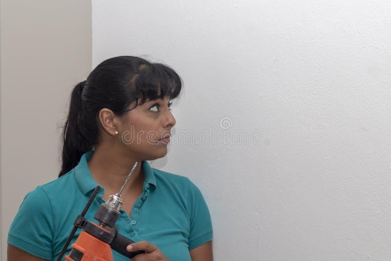 Parede latino da perfuração da mulher É autorizada mas a broca tem a foto de stock