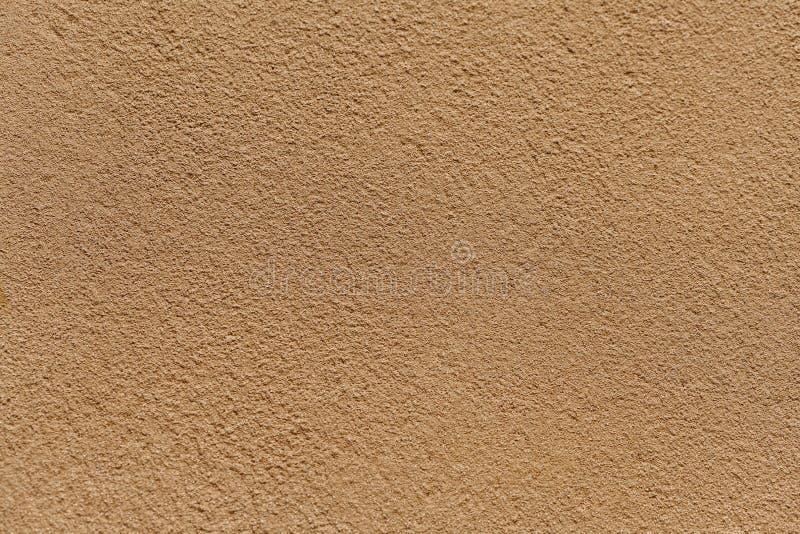 Parede leve velha da areia coberta com o emplastro desigual gasto Textura da superfície de pedra dourada do vintage foto de stock royalty free